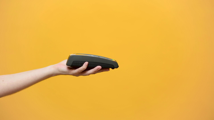 Close up cropped of female hold in hand wireless modern bank payment terminal to process acquire credit card payments black card isolated on yellow background. Copy space mock up advertising, man pay