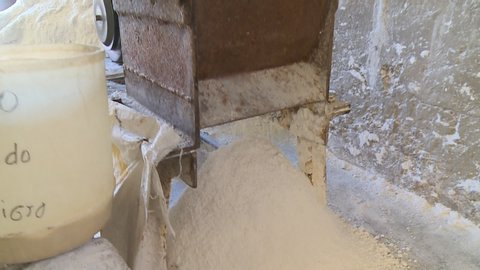 close-up low-angle still shot of dried raw salt being crushed using a local processing machine, Uyuni, Bolivia
