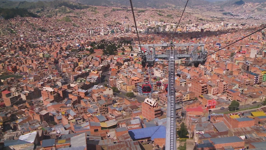 Wide low-angle back shot from a transiting cable car of an opposite moving cabin above La Paz city buildings, Bolivia