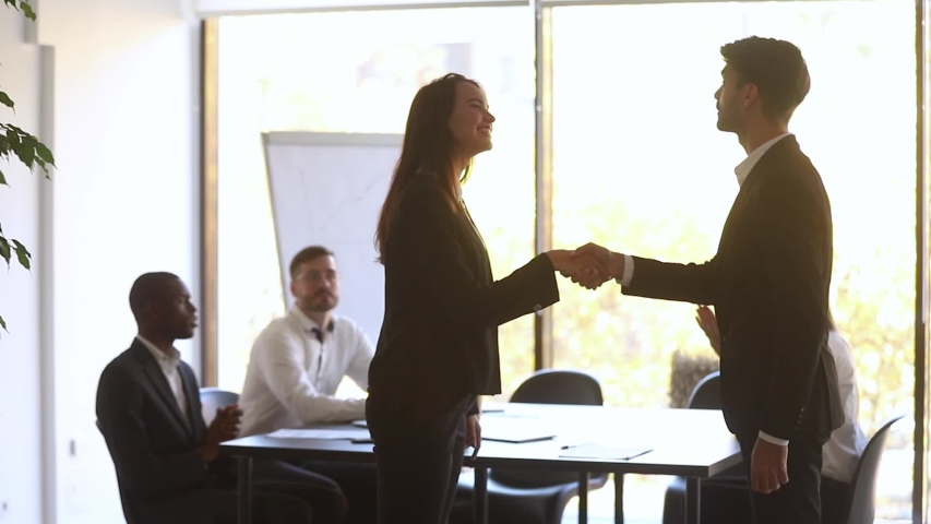 Happy manager handshake promote praise female employee for good work in office, overjoyed woman employee get appreciated rewarded with team applause shake hand of boss, respect recognition concept  #1030504763