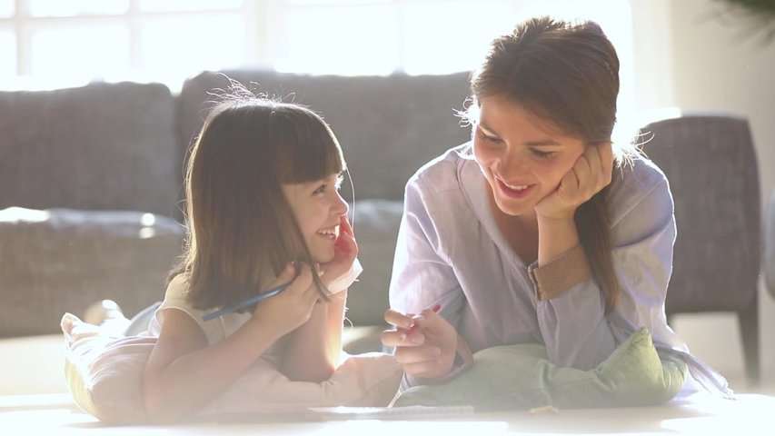 Caring mom babysitter teaching coloring drawing with pencils talking to little girl at home in lit with sunlight room, happy mother and child daughter play together enjoy creative kid parent activity