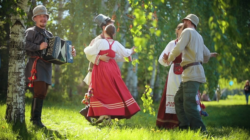 Two couples in traditional Russian clothes dancing on the field by the accordion music