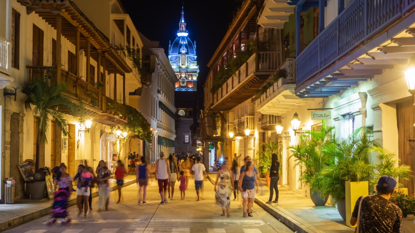Cartagena de Indias, Colombia - December 10: Zoom in time lapse view of tourists on the streets of the Walled City showing architectural landmark Cartagena Cathedral at night.