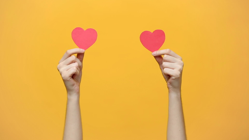 Female blogger hold in hands little red hearts, dancing to music rhythm isolated on yellow orange background. Like blogging blog social network tenderness concept. Valentines day international women  | Shutterstock HD Video #1030517558