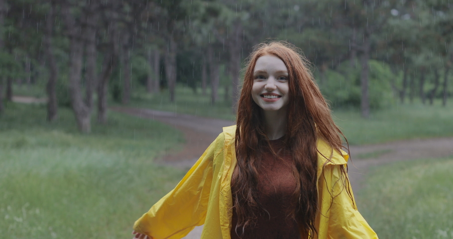 Attractive red-haired young woman in a yellow rain coat walking in the forest. The girl laughs and rejoices in the spring warm rain. tracking shot. in slow motion. Shot on Canon 1DX mark2 4K camera