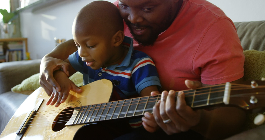 Front view of African american father teaching his son how to play guitar at home. Social distancing and self isolation in quarantine lockdown for Coronavirus Covid19 Royalty-Free Stock Footage #1030525814