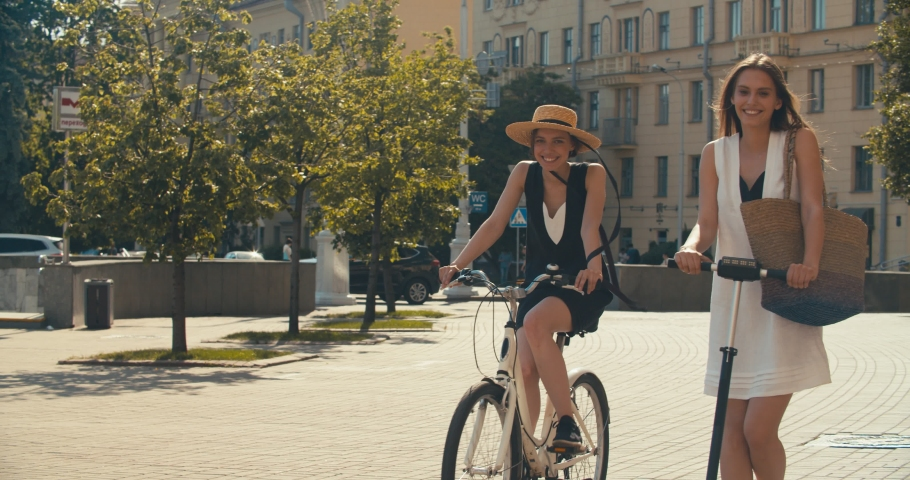 Two women walking together on street. Lifestyle and health in city. Girls riding vintage bike and electric scooter on urban background. 4K slow motion video footage 60 fps | Shutterstock HD Video #1030533134