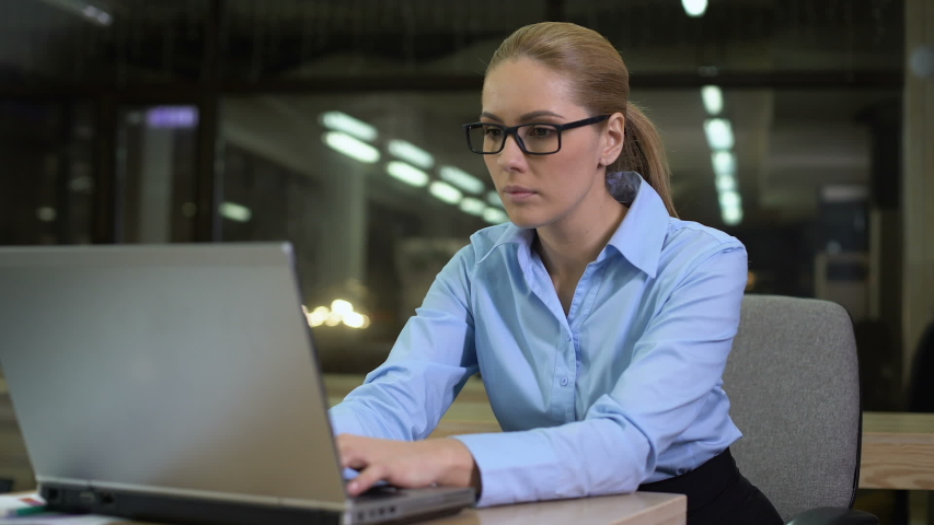 Happy businesswoman rejoicing successful startup, sitting in office at night   Shutterstock HD Video #1030536860