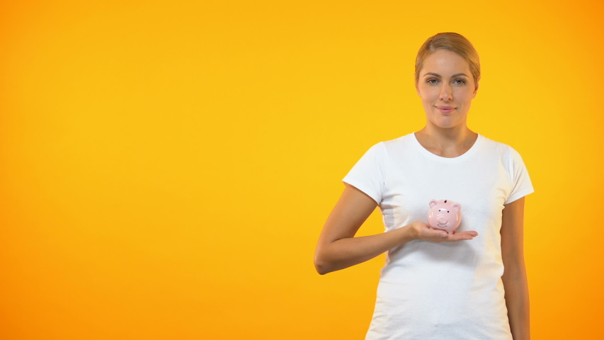 Positive female putting coin in piggybank, planning budget, financial savings | Shutterstock HD Video #1030538051