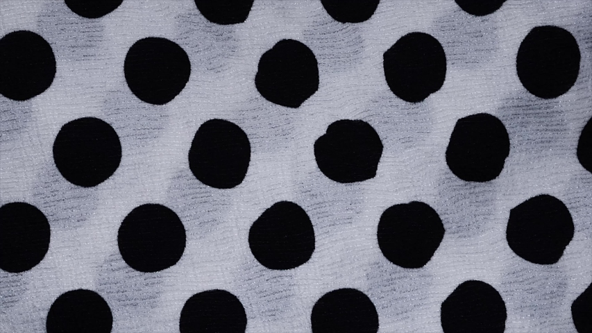 Spotted fabric cloth close up shot. Black dots on white background, Monochrome pattern.    Shutterstock HD Video #1030554200