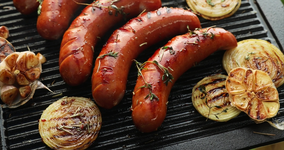 Grilling sausage with the addition of herbs and vegetables on the grill plate, outdoors. Grilling food, bbq, barbecue, 4k | Shutterstock HD Video #1030569140
