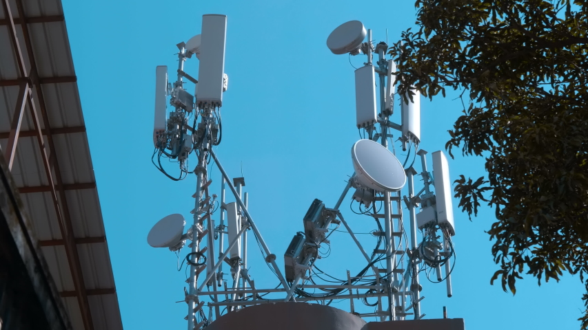 High telecommunication tower standing in Delhi, India. On it are satellite dishes, mobile communication antennas, a radio relay dishes, blocks of the radio module of the base station equipment Royalty-Free Stock Footage #1030573607
