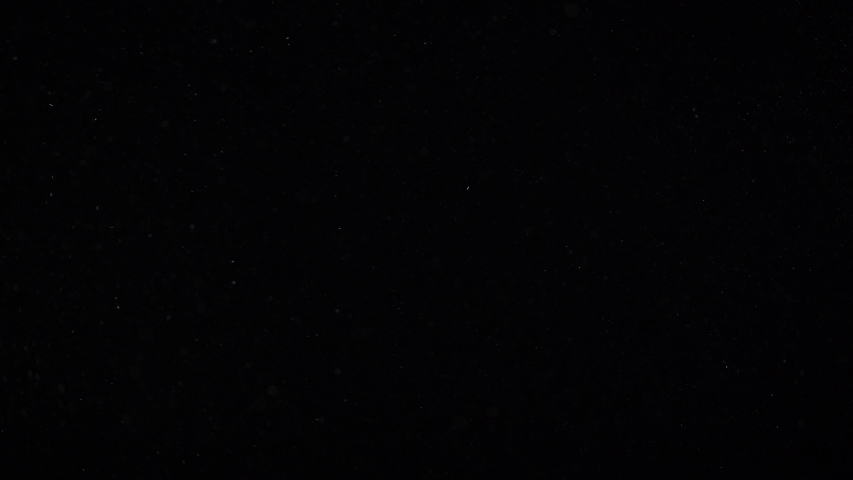 Floating miniature dust particles are soaring on a black background. Twirling randomly as if blown by wind moving quickly through space. Each of them flying independently and dynamically. | Shutterstock HD Video #1030576787
