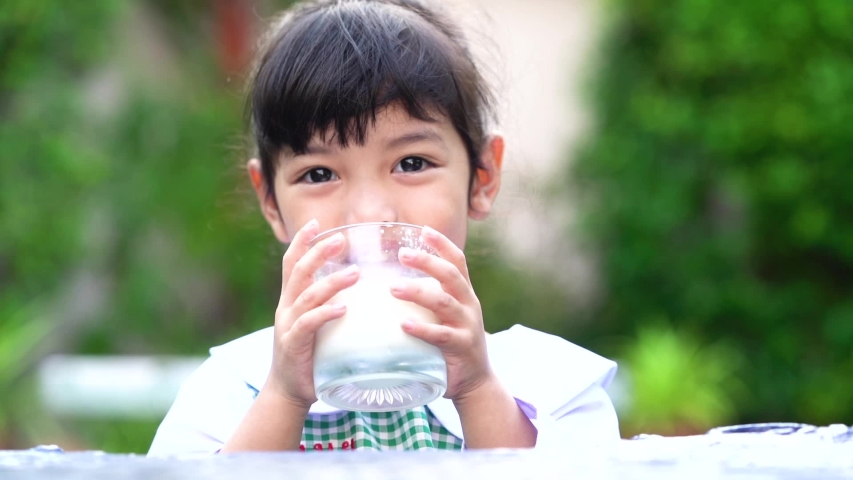 Asian cute student girl drinking a glass of milk at home before going to school in the morning. The concept is healthy and intelligent kid concept.