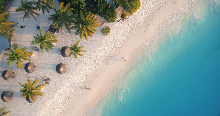 Aerial view of sea waves, umbrellas, palm trees and walking people on sandy beach at sunset. Summer in Zanzibar, Africa. Tropical landscape with parasols, sand, blue water. Top view from drone. Travel #1030586498