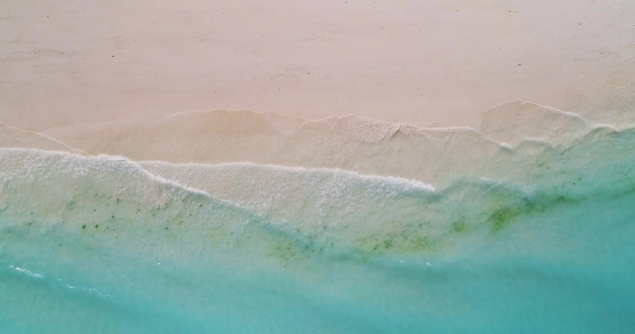 Aerial view of a transparent blue sea with beautiful waves at sunny day in summer. Tropical landscape from the air of ocean with azure water, sandy bottom at sunset. Top view from flying drone. Nature | Shutterstock HD Video #1030586519