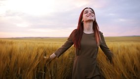 Romantic and carefree young woman in slow motion video walking on field wheat enjoying freedom and calmness on rural nature during vacations holidays. Incredible colorful sunset