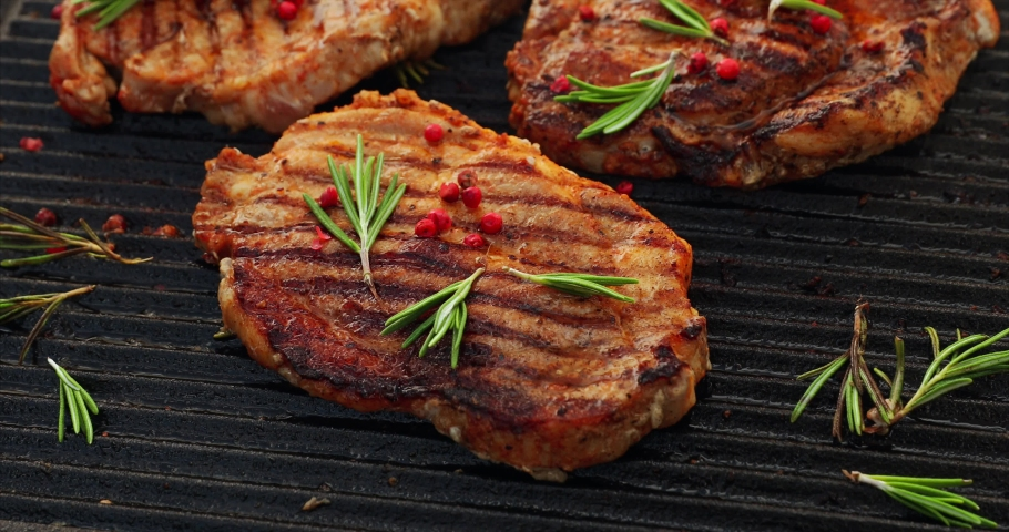 Grilling pork steaks, pork neck with the addition of herbs and spices on the grill plate, top view, 4k. Grilled meat, bbq, barbecue | Shutterstock HD Video #1030608836