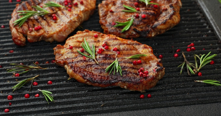 Grilling pork steaks, pork neck with the addition of herbs and spices on the grill plate, top view, 4k. Grilled meat, bbq, barbecue | Shutterstock HD Video #1030608839