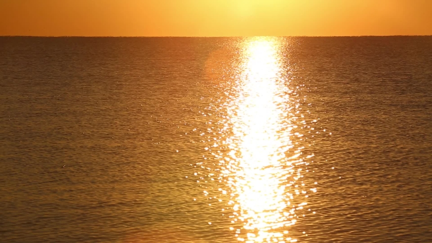 Blurred reflected in the sea sun ray and sunrise over the calm sea. the sun rises right above the sea and a big beautiful ray is reflected on the surface of the water. the sky is filled with golden