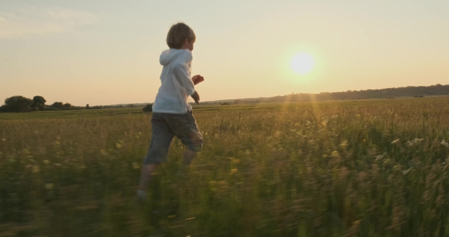 Happy child running on the meadow in the summer while sunset. Happy 7 year old cheerful boy runs and looks back, on field. Happiness concept. Active smiling boy on nature in spring. Slow motion     | Shutterstock HD Video #1030680677