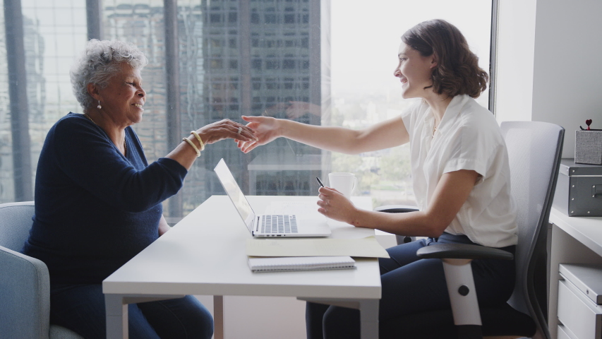 Senior Woman Meeting With Female Financial Advisor In Office And Signing Contract