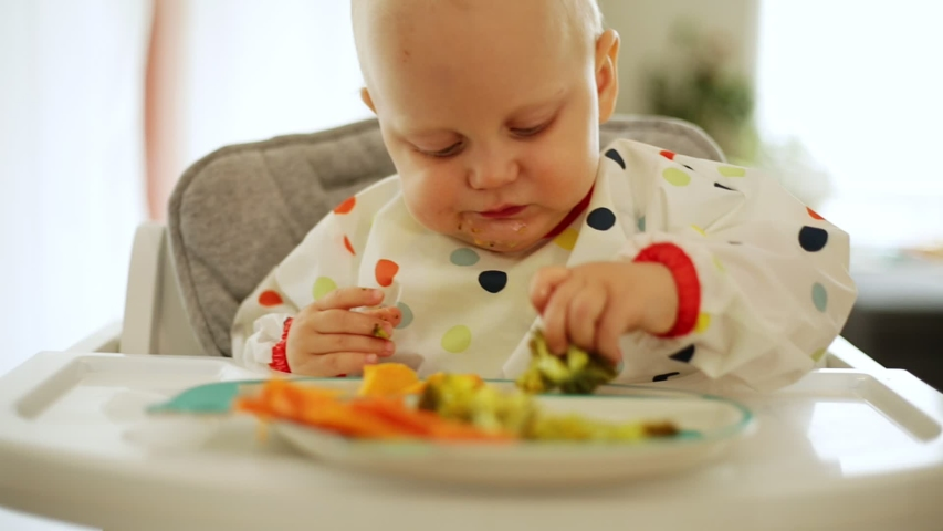Child eating carrot and broccoli with BLW method, baby led weaning. Happy vegetarian kid eating lunch. Toddler eat himself, self-feeding. | Shutterstock HD Video #1030695377