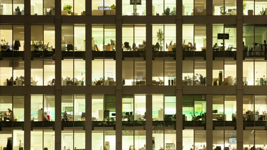 LONDON / UNITED KINGDOM  - OCTOBER 2016 : Timelapse of the exterior of an office block at night revealing the daily activity of office workers night themes of routines working late
