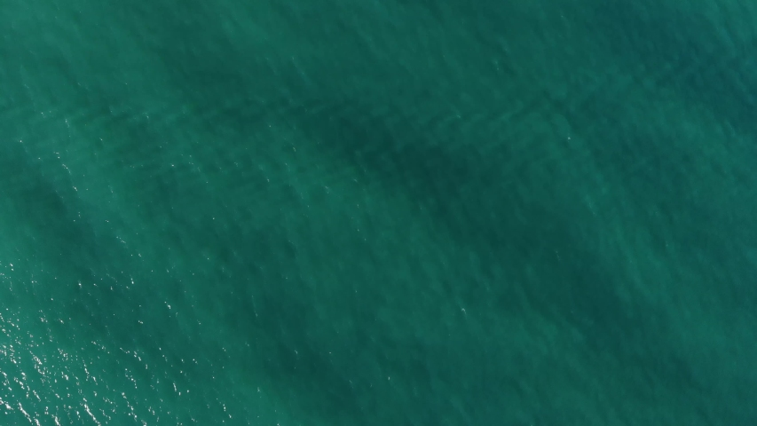 Aerial top down view from high altitude of green sea water texture. The camera flies over the water, a view of the water surface. Background of the water surface. 4K aerial view