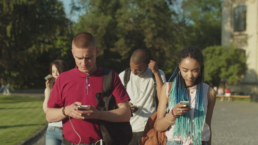 Group of multinational college students obsessed with smartphones walking, ignoring everything around them on university campus. Multi ethnic young people phubbing each other using mobile app outdoors Royalty-Free Stock Footage #1030736186