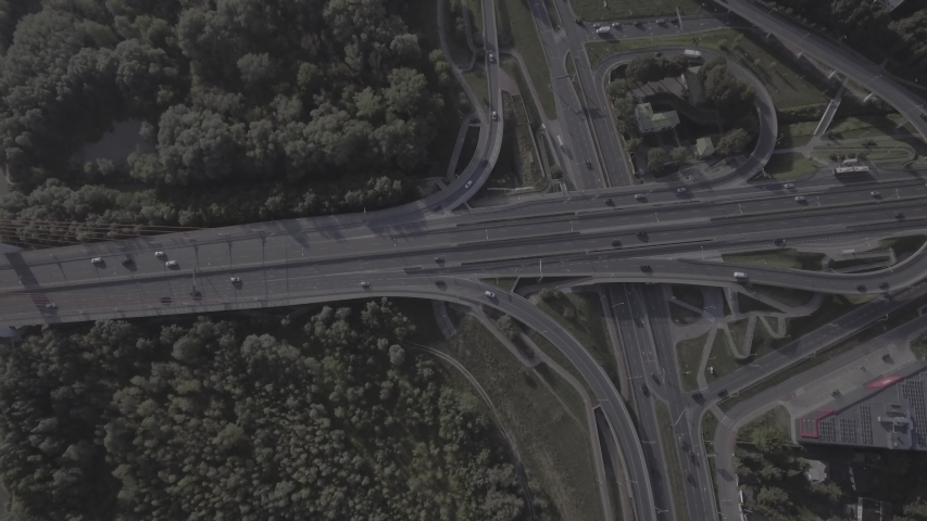 Aerial view of a multi-level junction highway passing through a bridge on the outskirts of Warsaw. Filmed from 4K drone in RAW. Video for post-processing. | Shutterstock HD Video #1030737791