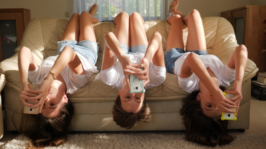 Teenager girls triplet sisters at home watch smart phones in social media lying on couch upside down #1030744325