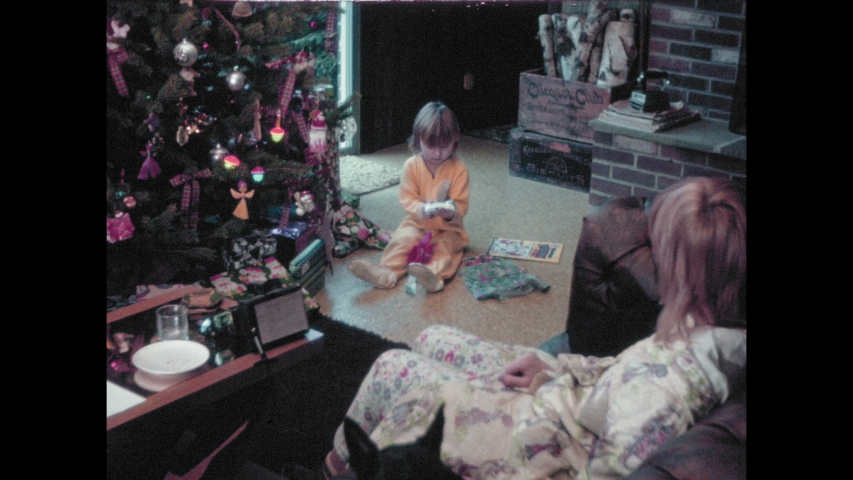 1970s: Woman, child, and dog sit in living room. Child opens Christmas presents. Girl sits in front of Christmas tree, plays with puppets, man watches.