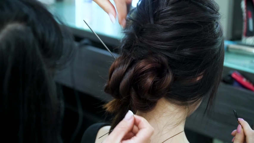 Fixing hair strands in the hair with a hairpin. The hairdresser makes a trendy, festive hairstyle with long hair | Shutterstock HD Video #1030753991