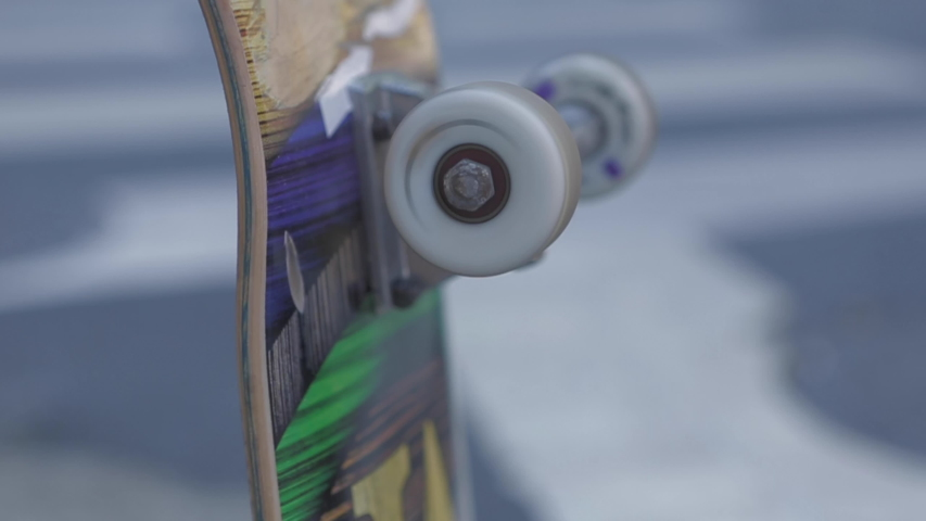 Skateboard wheels spinning in close up shot, green, yellow and blue board is held by a skater boy, Tilt up slow motion 4K. Street in blurred background.