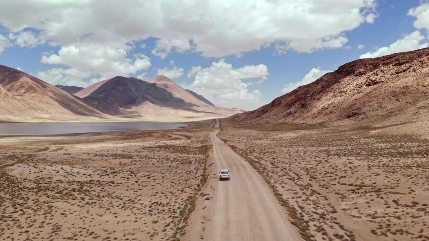 Aerial over off road 4x4 car driving along gravel trail path near arid desert mountains.Pamir Highway silk road trip adventure in Kyrgyzstan and Tajikistan desert,central Asia.4k drone flight video | Shutterstock HD Video #1030757972