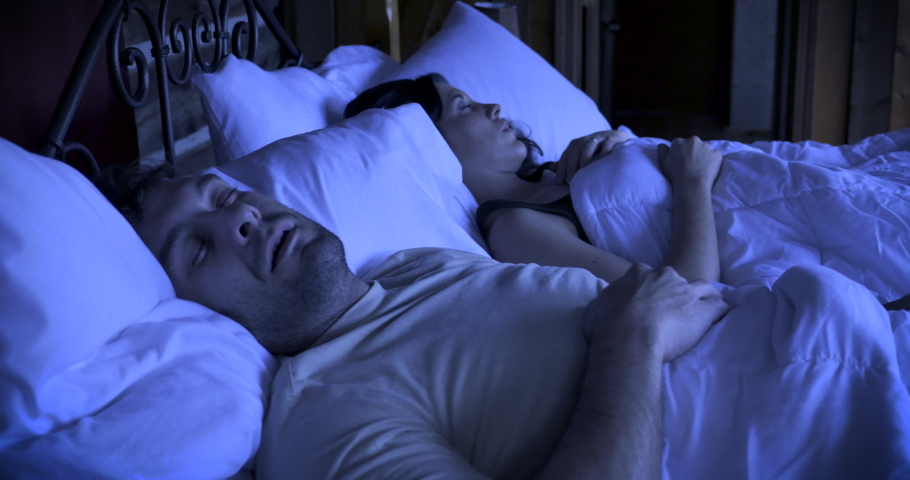 Man reluctantly wakes up in the dark from an alarm or phone call on his mobile device while lying in bed next to a woman | Shutterstock HD Video #1030758038