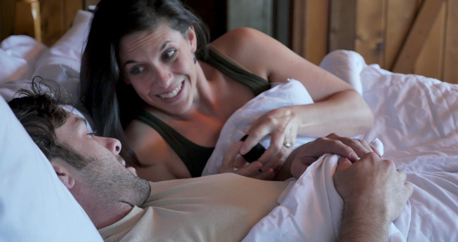 Young pretty woman proposing to a handsome man giving him an engagement ring in bed | Shutterstock HD Video #1030758080