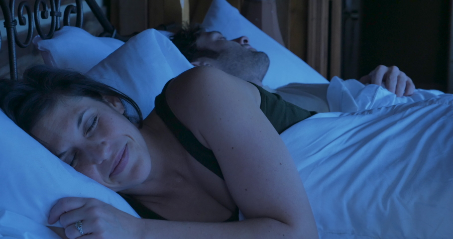 Attractive woman going to sleep with a smile on her face content, and relaxed next to a man lying in bed next to her