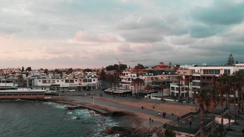 Drone shot of the touristic area in the city with pier and cafes. Tourists walking near pier and taking photos. Aerial drone view of city with mountain landscape.