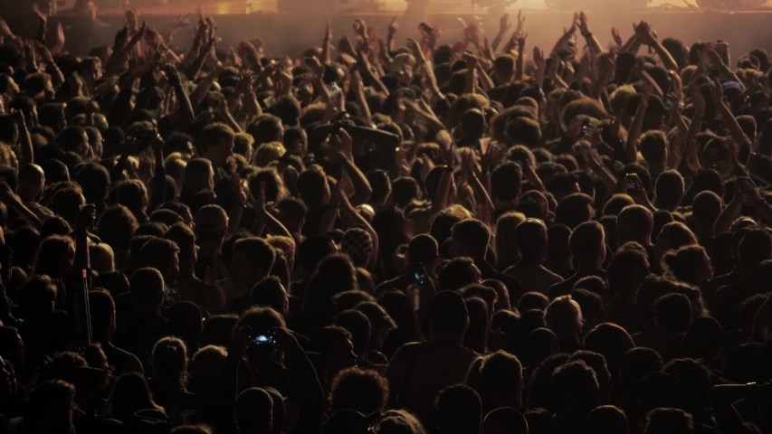 Big crowd of people dancing on music festival concert at night, street music big event applause raising hands | Shutterstock HD Video #1030762991