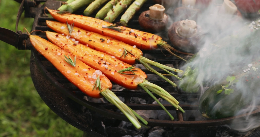 Grilling vegetables with the addition of spices and herbs on the grill plate outdoors. Vegan grilled food, 4k