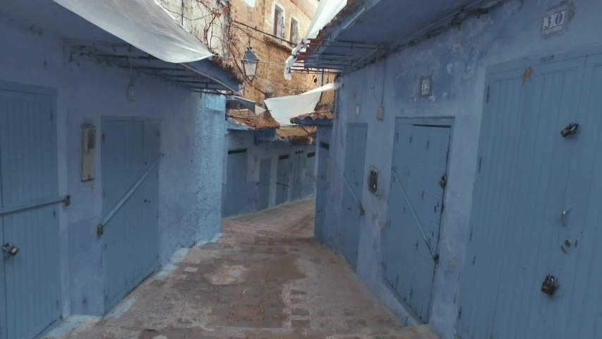 Smooth camera steady slide shot around old neighboord narrow street with white and blue walls, beautiful doors flowers, in Chefchaouen, blue city Morocco, no people | Shutterstock HD Video #1030795166