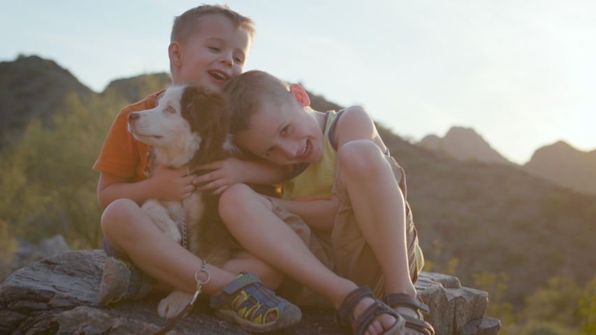 Two young boys hug their puppy outside at sunset. Shot on a Canon C200 in 4K in Phoenix, Arizona in 2019.