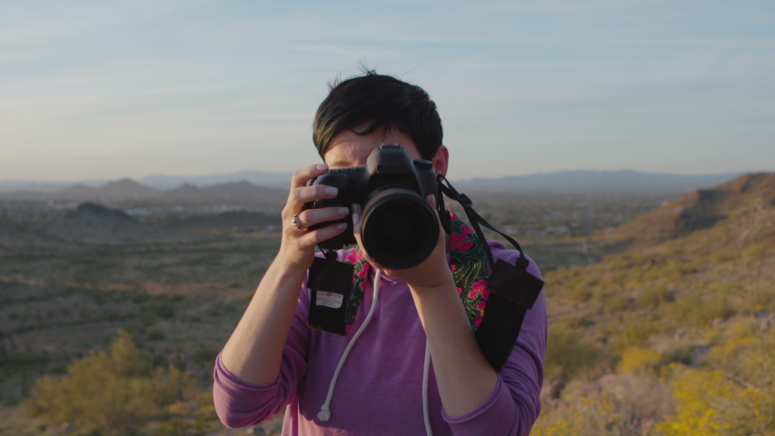 Proud photographer holding a camera and taking pictures by sunset in the desert. Shot on a Canon C200 in 4K in Phoenix, Arizona in 2019.