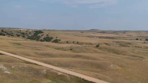 Aerial drone shot panning around rolling hills and plains in South Dakota.