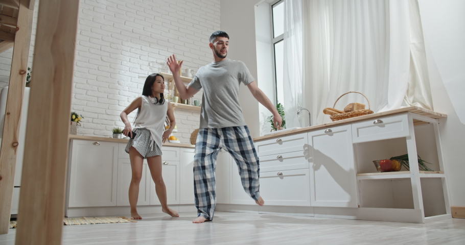 Pretty interracial couple wearing pyjamas funnily dancing and singing early in morning, preparing for new day, spending time together, having fun 4k #1030825781