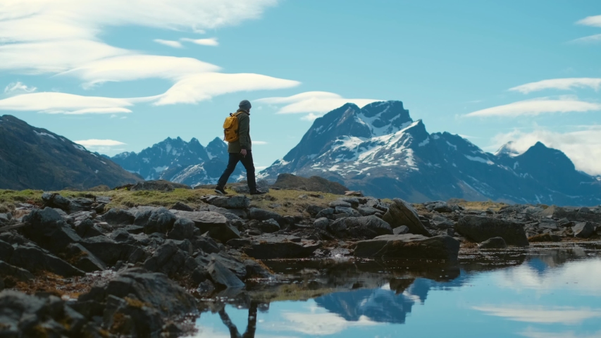 Young bearded man in a hat with a backpack comes down from the mountains on a background of snow capped mountains Royalty-Free Stock Footage #1030837142