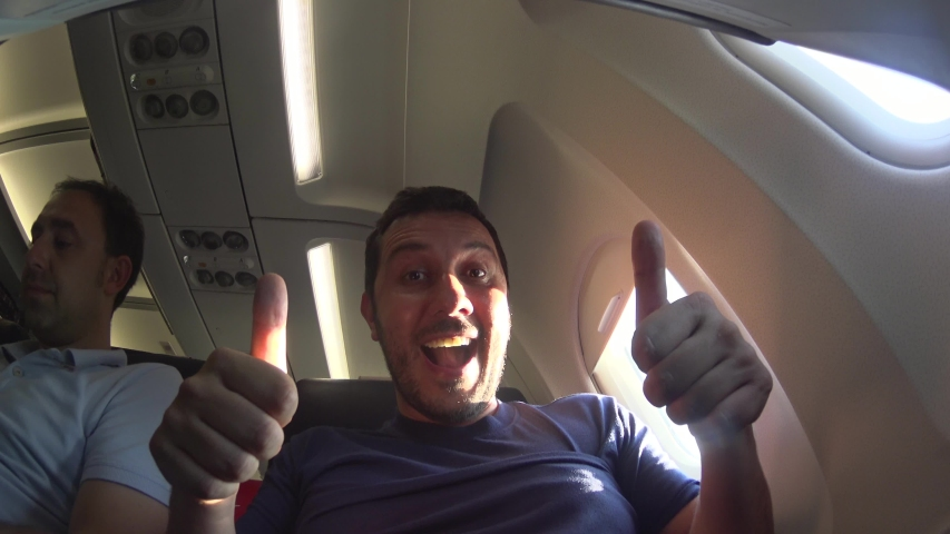 Handsome man travel take photo selfie inside airplane - Cheerful tourist taking self photo with mobile phone into airplane - Concept of happiness and holidays | Shutterstock HD Video #1030837604