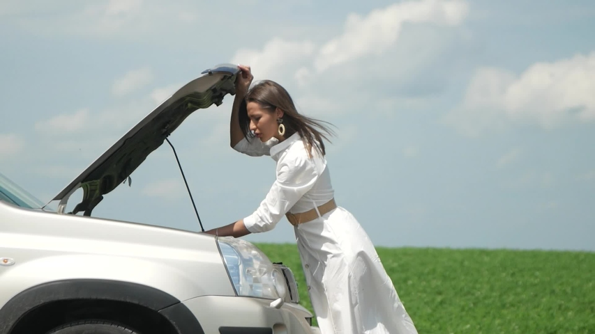 Business woman waits for assistance near her car broken down on the road side, having trouble with her broken car, emergency service on the road